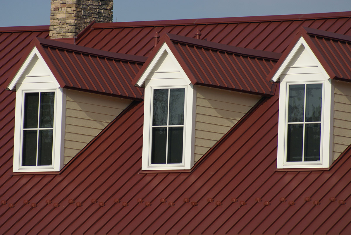Attic windows covered with metal roof and siding